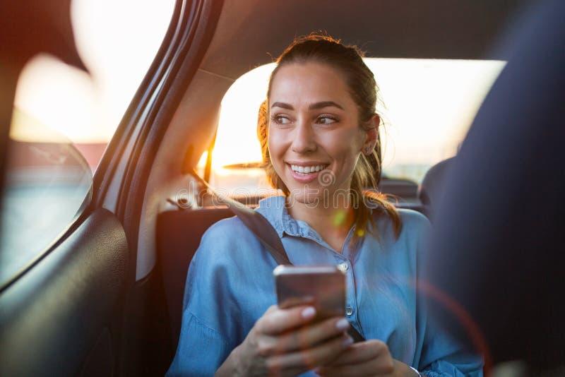 Γυναίκα με το τηλέφωνο στη πίσω θέση ενός αυτοκινήτου στοκ εικόνες