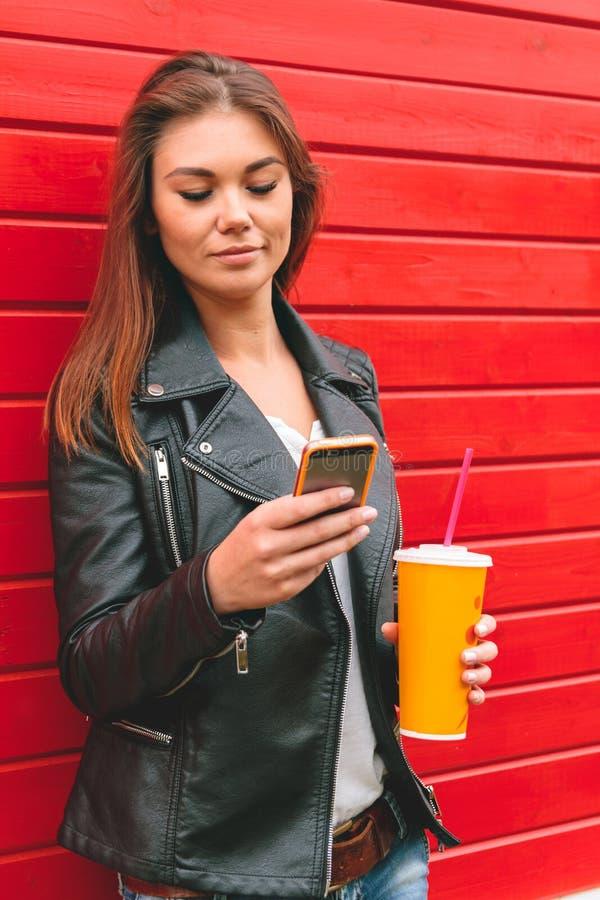 Γυναίκα με το τηλέφωνο και ένα ποτό υπό εξέταση στοκ εικόνα