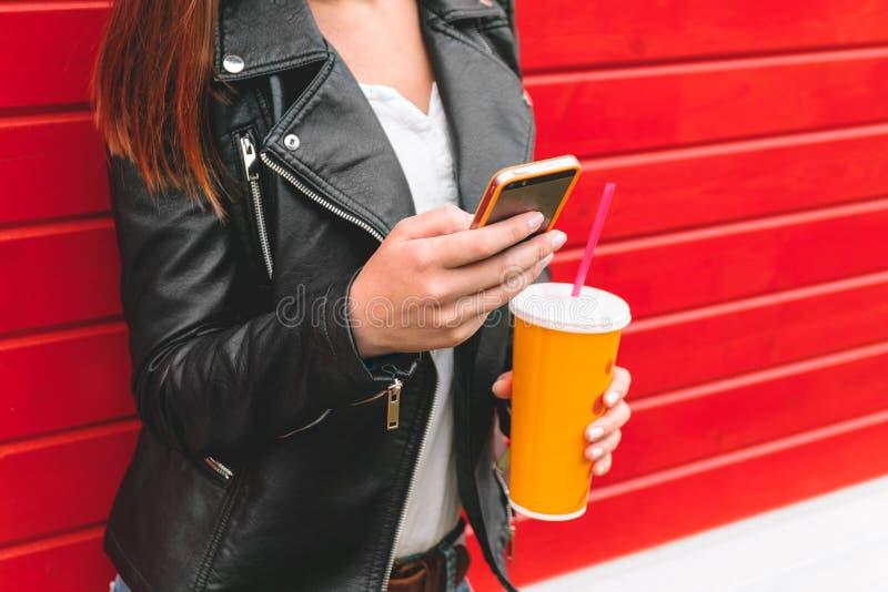 Γυναίκα με το τηλέφωνο και ένα ποτό υπό εξέταση στοκ φωτογραφίες με δικαίωμα ελεύθερης χρήσης