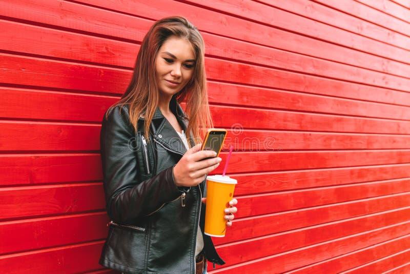 Γυναίκα με το τηλέφωνο και ένα ποτό υπό εξέταση στοκ εικόνες