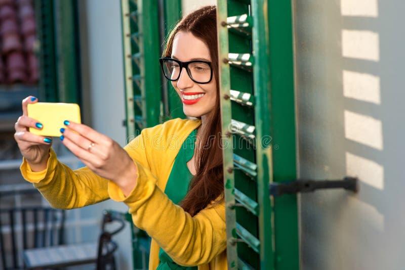 Γυναίκα με το τηλέφωνο στο μπαλκόνι στοκ εικόνα