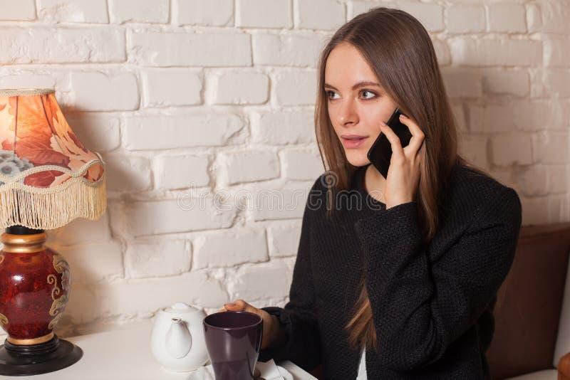Γυναίκα με το τσάι και το smartphone στοκ εικόνα