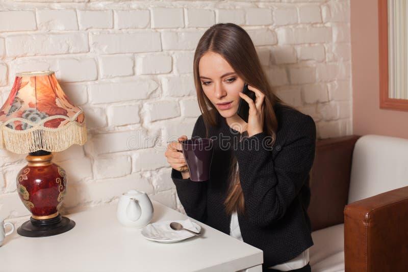 Γυναίκα με το τσάι και το smartphone στοκ φωτογραφία
