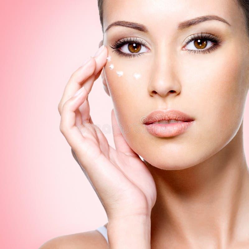 Γυναίκα με το υγιές πρόσωπο που εφαρμόζει την καλλυντική κρέμα κάτω από τα μάτια στοκ εικόνες