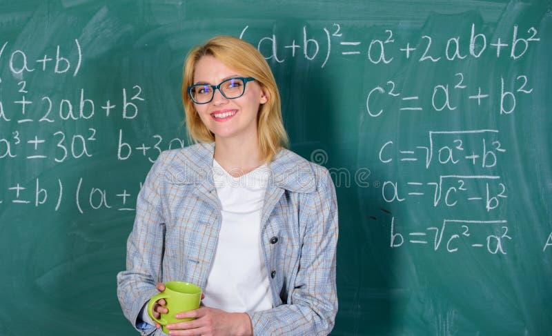 Γυναίκα με το υπόβαθρο πινάκων κιμωλίας φλυτζανιών τσαγιού Αποτρέψτε την έννοια ουδετεροποίησης χαλαρώστε το χρόνο Ο δάσκαλος πίν στοκ φωτογραφία με δικαίωμα ελεύθερης χρήσης