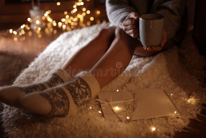 Γυναίκα με το φλυτζάνι του καυτών ποτού και του βιβλίου στο σπίτι το χειμερινό βράδυ στοκ φωτογραφία