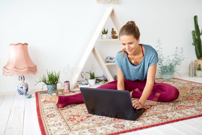 Γυναίκα με το φορητό προσωπικό υπολογιστή στο στούντιο γιόγκας στοκ εικόνες
