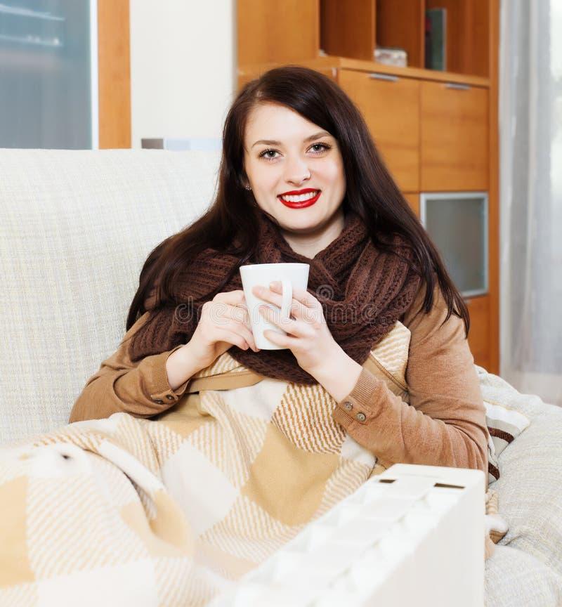 Γυναίκα με το φλυτζάνι κοντά στην ηλεκτρική θερμάστρα στοκ φωτογραφία με δικαίωμα ελεύθερης χρήσης