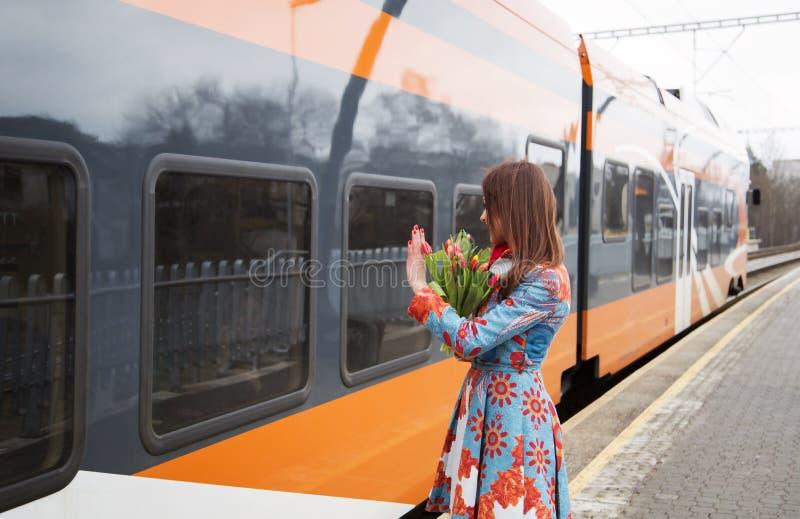 Γυναίκα με το χαιρετισμό λουλουδιών για να εκπαιδεύσει passanger στοκ εικόνες