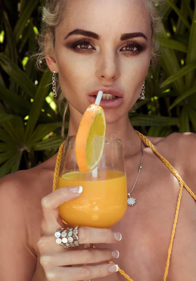 Γυναίκα με το χυμό από πορτοκάλι στο τροπικό ξενοδοχείο θερέτρου στοκ φωτογραφία