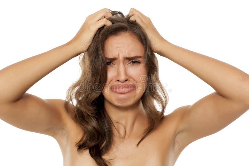 Γυναίκα με το itchy κρανίο στοκ φωτογραφία