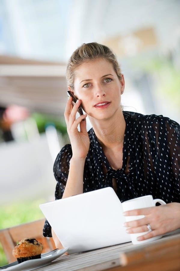Γυναίκα με το lap-top και το τηλέφωνο στοκ εικόνα με δικαίωμα ελεύθερης χρήσης