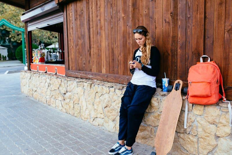 Γυναίκα με το longboard και σακίδιο πλάτης που χρησιμοποιούν το τηλέφωνο κυττάρων της γυναίκα που στέλνει ένα μήνυμα κειμένου από στοκ φωτογραφία