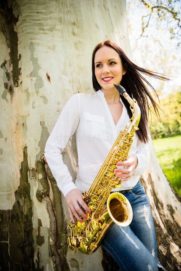 Γυναίκα με το saxophone στη φύση στοκ εικόνα