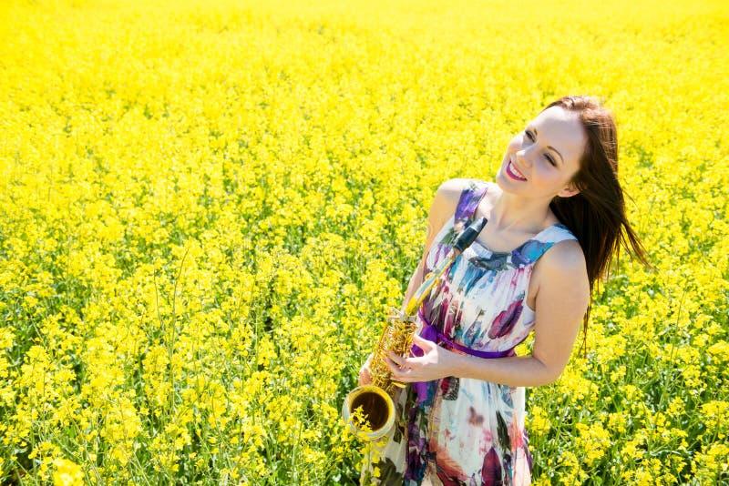 Γυναίκα με το saxophone στον τομέα συναπόσπορων στοκ φωτογραφία με δικαίωμα ελεύθερης χρήσης