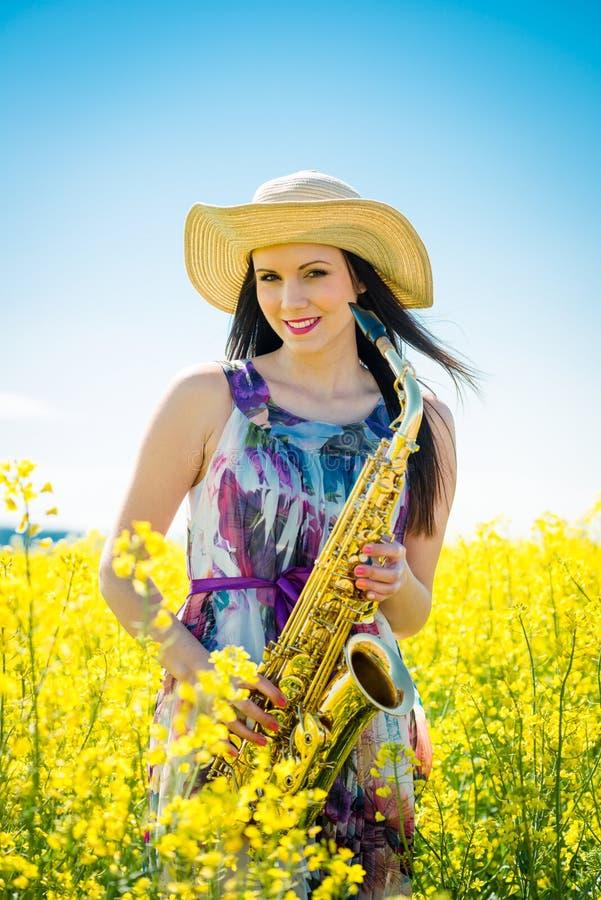 Γυναίκα με το saxophone στον τομέα συναπόσπορων στοκ εικόνα με δικαίωμα ελεύθερης χρήσης