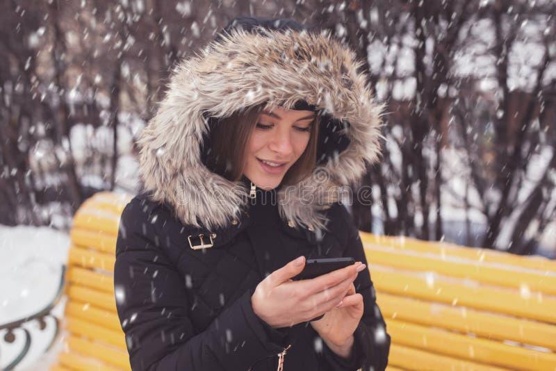 Γυναίκα με το smartphone κάτω από τα showflakes στοκ φωτογραφίες