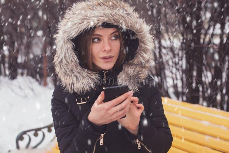 Γυναίκα με το smartphone κάτω από τα showflakes στοκ εικόνες
