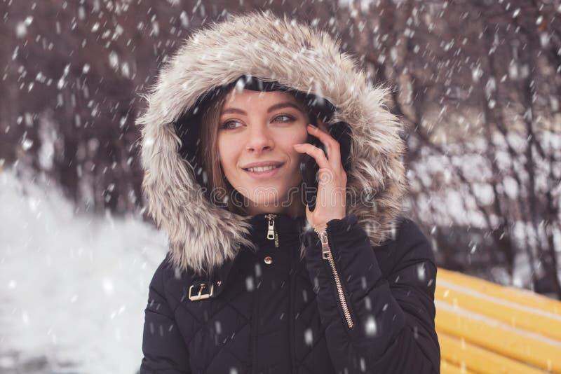 Γυναίκα με το smartphone κάτω από τα showflakes στοκ φωτογραφία με δικαίωμα ελεύθερης χρήσης