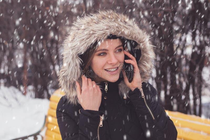 Γυναίκα με το smartphone κάτω από τα showflakes στοκ φωτογραφίες με δικαίωμα ελεύθερης χρήσης