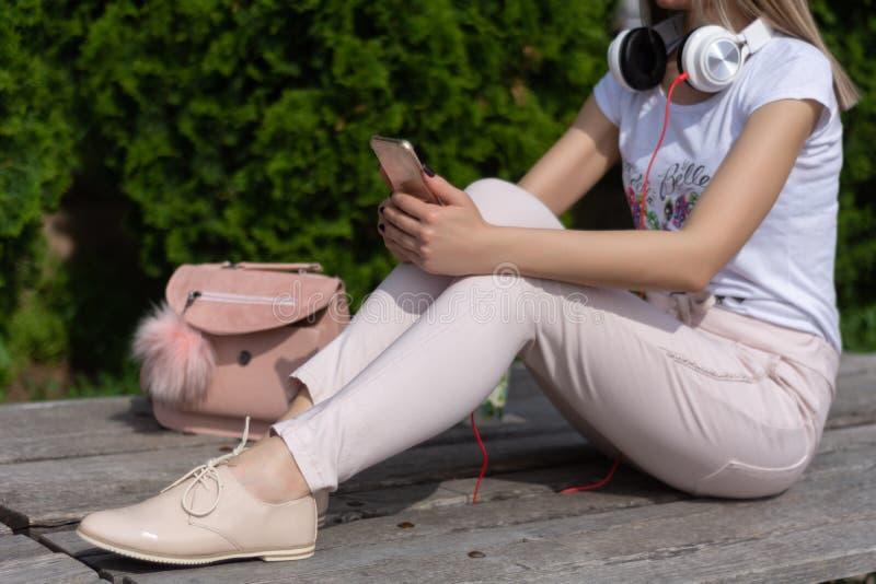 Γυναίκα με το smartphone στα πόδια και τα ακουστικά γύρω από τη συνεδρίαση λαιμών σε έναν πάγκο σε ένα πάρκο και μια χαλάρωση στοκ εικόνα με δικαίωμα ελεύθερης χρήσης