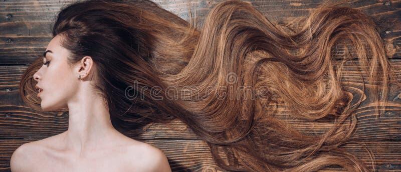 Γυναίκα με όμορφο μακρυμάλλη στο ξύλινο υπόβαθρο τρίχωμα μακρύ Καθιερώνοντα τη μόδα κουρέματα Κομμωτήριο ομορφιάς στοκ φωτογραφίες με δικαίωμα ελεύθερης χρήσης