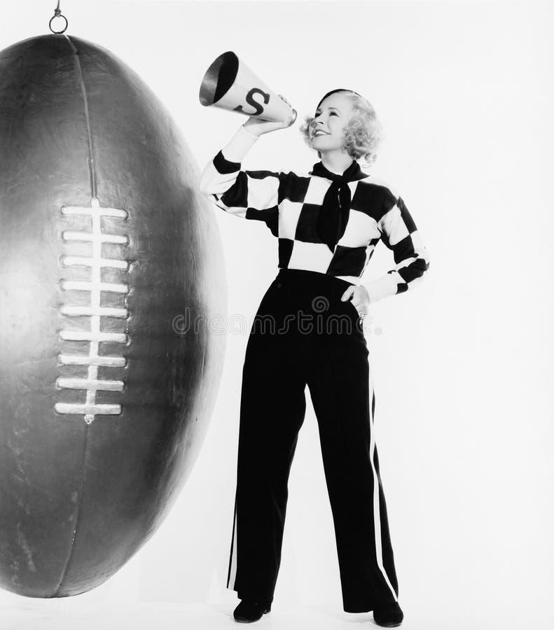 Γυναίκα με megaphone και το τεράστιο ποδόσφαιρο (όλα τα πρόσωπα που απεικονίζονται δεν ζουν περισσότερο και κανένα κτήμα δεν υπάρ στοκ εικόνες