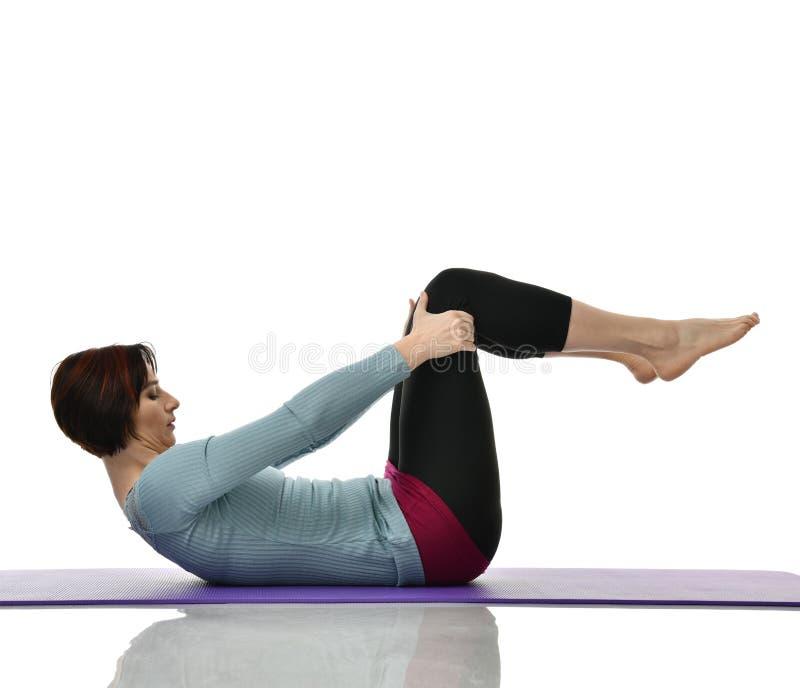 Γυναίκα μητέρων που ασκεί κάνοντας το μεταγεννητικό workout Ο θηλυκός εκπαιδευτικός ικανότητας κρατά τα πόδια στη γυμναστική και  στοκ φωτογραφίες