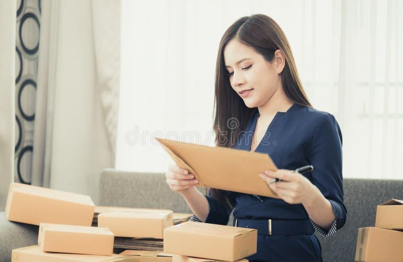 Γυναίκα μικρών επιχειρήσεων που προετοιμάζεται να στείλει το προϊόν της στα κιβώτια στοκ εικόνες
