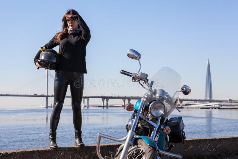 Γυναίκα μοτοσυκλετιστών που στέκεται στην ολόκληρη κοντινή μοτοσικλέτα αναχωμάτων, που κρατά το μαύρο κράνος, κόλπος θάλασσας με  στοκ φωτογραφία