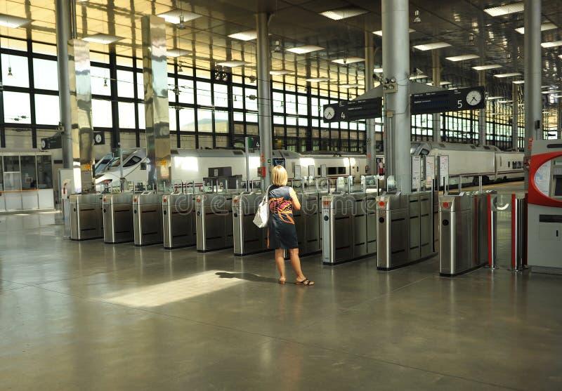 Γυναίκα μπροστά από τις μηχανές στροφής ελέγχου, σιδηροδρομικός σταθμός Καντίζ, Ανδαλουσία, Ισπανία στοκ εικόνα