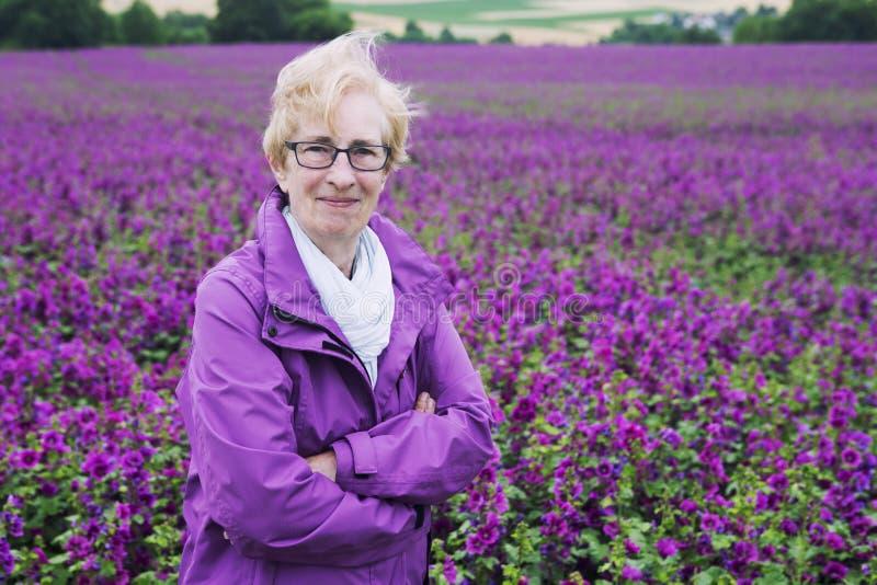 Γυναίκα μπροστά από τον τομέα λουλουδιών που χαμογελά στη κάμερα στοκ εικόνα