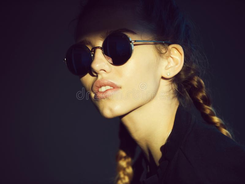 Γυναίκα μόδας με το λατρευτό πρόσωπο και κοτσίδες στα μοντέρνα γυαλιά ηλίου στοκ εικόνες