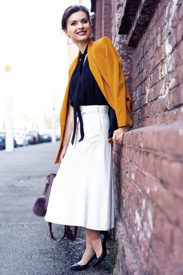 Γυναίκα μόδας πορτρέτου που περπατά στην οδό Φορά το κίτρινο σακάκι, χαμογελώντας στην πλευρά στοκ εικόνες