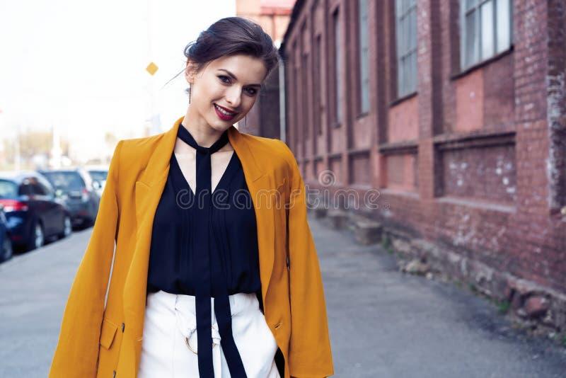 Γυναίκα μόδας πορτρέτου που περπατά στην οδό Φορά το κίτρινο σακάκι, χαμογελώντας στην πλευρά στοκ φωτογραφία με δικαίωμα ελεύθερης χρήσης