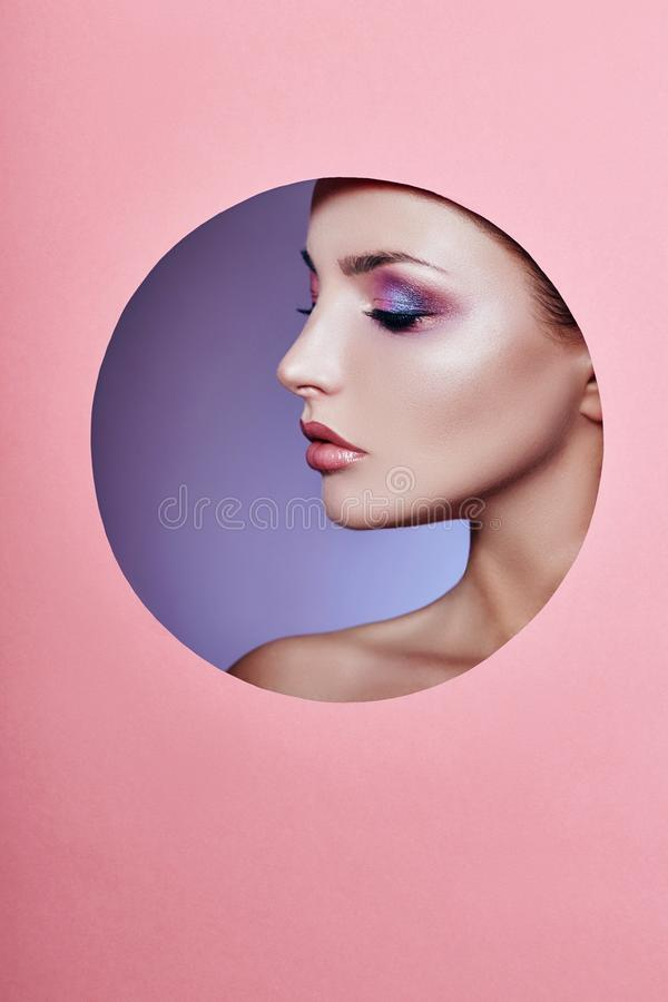 Γυναίκα μόδας φύσης καλλυντικών ομορφιάς makeup σε έναν στρογγυλό κύκλο τρυπών στο ρόδινο έγγραφο, διαστημική διαφήμιση αντιγράφω στοκ εικόνα με δικαίωμα ελεύθερης χρήσης