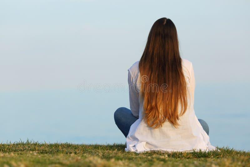 Γυναίκα μόνο που προσέχει τη συνεδρίαση ουρανού στη χλόη στοκ φωτογραφία