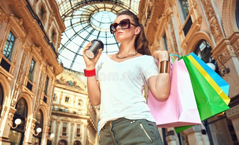 Γυναίκα μόδας με τις τσάντες αγορών και φλυτζάνι καφέ σε Galleria στοκ φωτογραφία