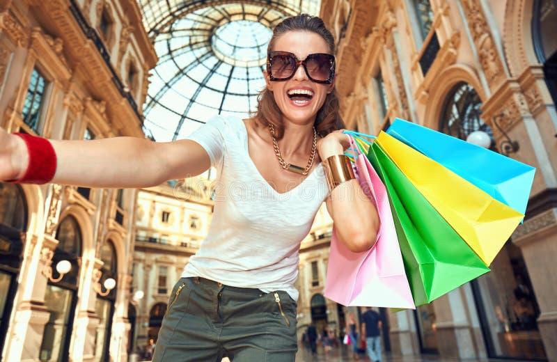 Γυναίκα μόδας με τις τσάντες αγορών που παίρνουν selfie σε Galleria στοκ εικόνες