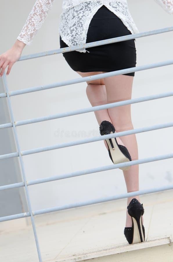 Γυναίκα μόδας που κλίνει ενάντια σε ένα κιγκλίδωμα σιδήρου στοκ φωτογραφία με δικαίωμα ελεύθερης χρήσης