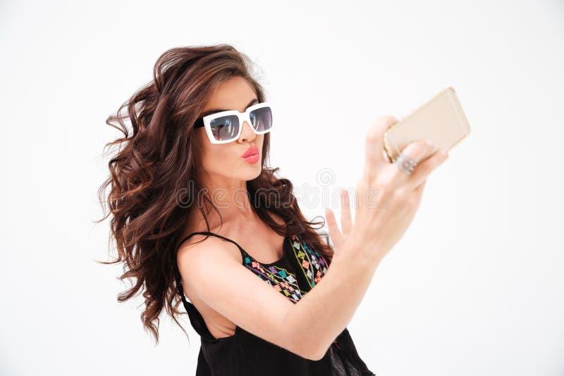 Γυναίκα μόδας στα γυαλιά ηλίου που κάνει selfie τη φωτογραφία στο smartphone στοκ φωτογραφία