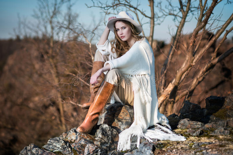 Γυναίκα μόδας στη συνεδρίαση ύφους χωρών στο βράχο φαραγγιών στοκ φωτογραφία
