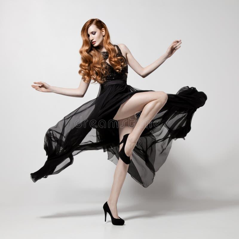 Γυναίκα μόδας στο κυματίζοντας μαύρο φόρεμα Άσπρη ανασκόπηση στοκ εικόνα