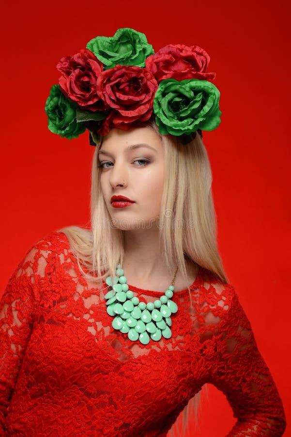Γυναίκα μόδας στο κόκκινο επικεφαλής στεφάνι φορεμάτων και λουλουδιών στοκ φωτογραφία με δικαίωμα ελεύθερης χρήσης