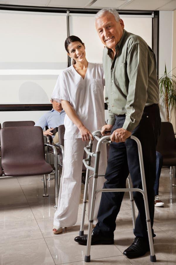 Γυναίκα νοσοκόμα που βοηθά τον ανώτερο ασθενή με τον περιπατητή στοκ εικόνες με δικαίωμα ελεύθερης χρήσης