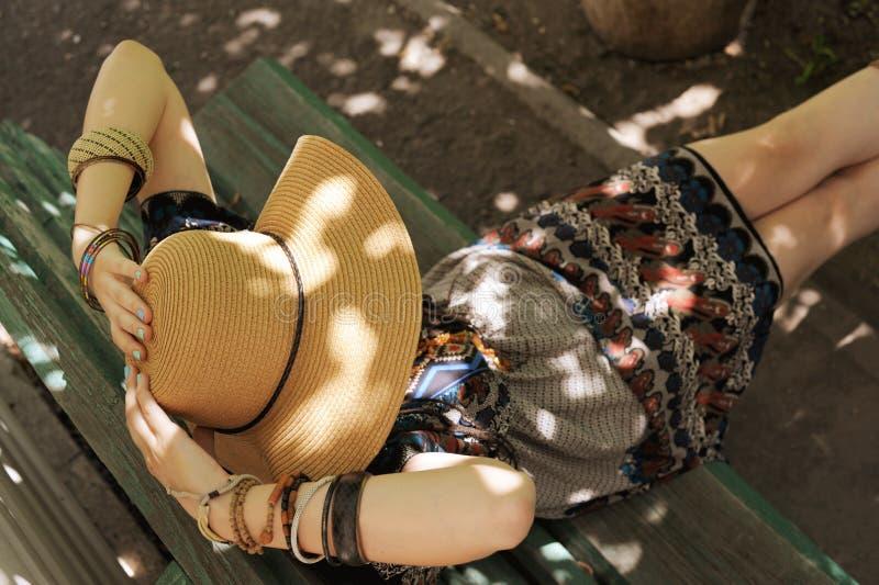 Γυναίκα ντυμένη με φορεσιά και καπέλο, καθισμένη σε ένα παγκάκι στοκ εικόνα με δικαίωμα ελεύθερης χρήσης
