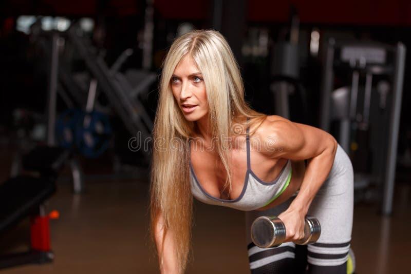 Γυναίκα ξανθή στη γυμναστική, που εκπαιδεύει με τους αλτήρες στοκ φωτογραφία με δικαίωμα ελεύθερης χρήσης