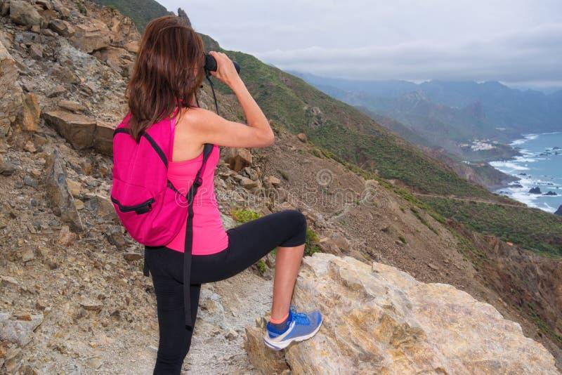 Γυναίκα οδοιπόρων πάνω από το βουνό που κοιτάζει μέσω των διοπτρών στοκ φωτογραφία με δικαίωμα ελεύθερης χρήσης