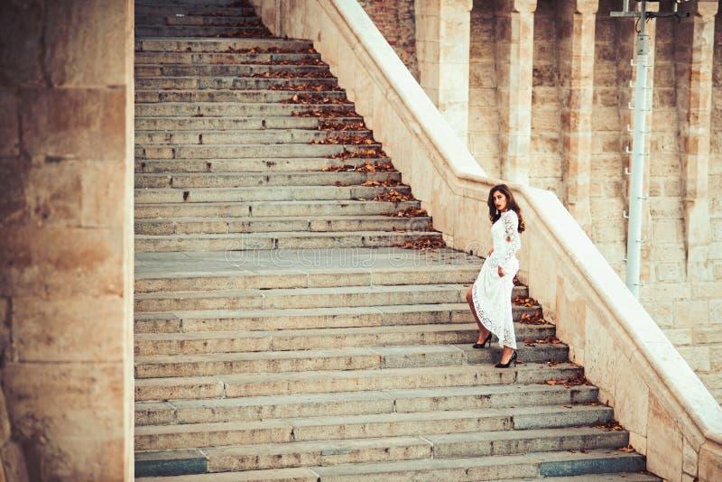 Γυναίκα ομορφιάς με μακρυμάλλη στα βήματα σκαλοπατιών Το κορίτσι ομορφιάς με τη γοητεία κοιτάζει στοκ εικόνες με δικαίωμα ελεύθερης χρήσης