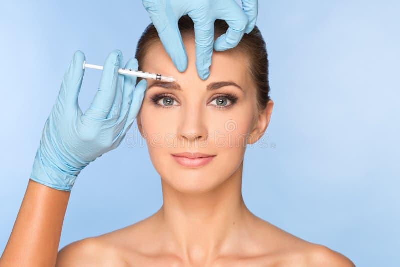 Γυναίκα ομορφιάς που δίνει botox τις εγχύσεις στοκ εικόνες